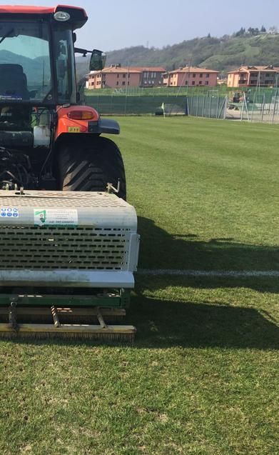 trattore all'opera del taglio manto erboso campo sportivo